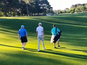 Three men walking into the sunlight hitting a patch of the golf course.