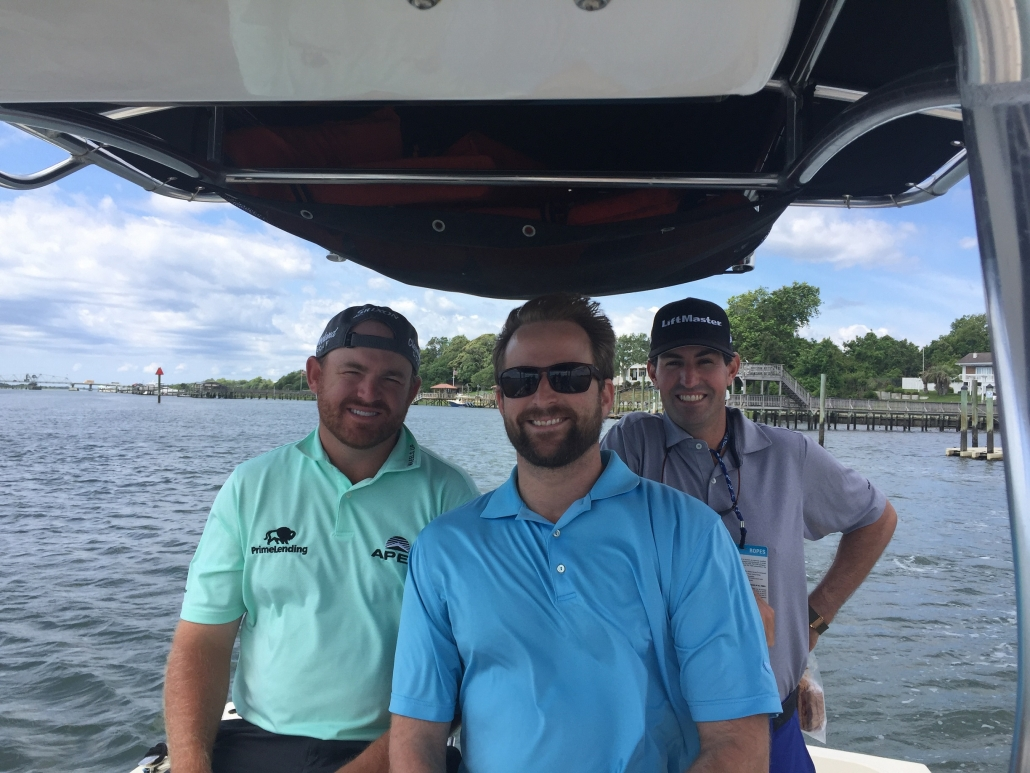 Three men smiling while sitting in a motor boat.