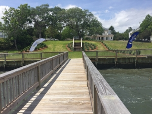 A pier from the view of the water looking inland. At the other end of the pier there are two MegaCorp flags blowing in the wind. In the distance there is a small set of stairs that leads up to the yard of a house.