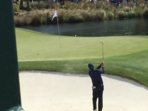 A man shortly after hitting a golf ball out of the sand trap. The ball is in the air, headed in the direction of the flag.
