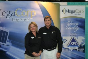 Denise and Ryan Legg standing in front of a wall with a MegaCorp Logistics decal.