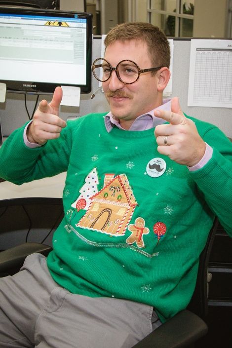 A young man sitting in an office cubicle, turned away from his computer. He is wearing big, round glasses and a green holiday sweater. He is smiling and is pointing his index fingers at the camera.