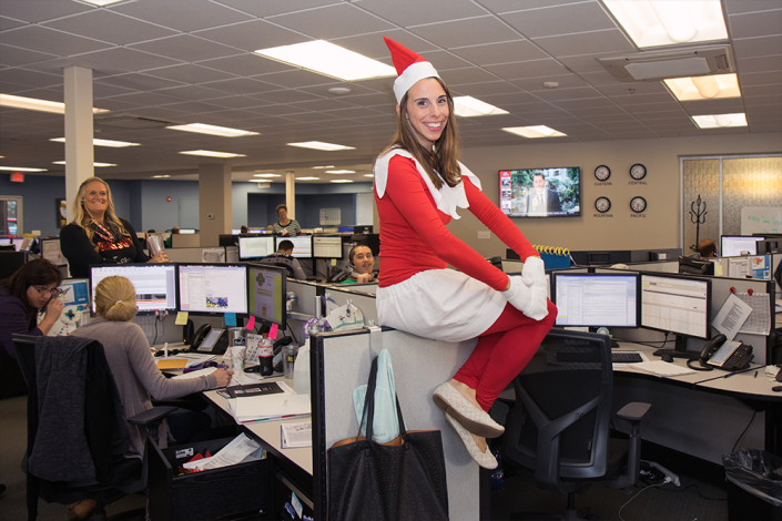 A young woman dressed as the Elf on a Shelf. She is sitting on top of the wall of a cubicle and smiling.