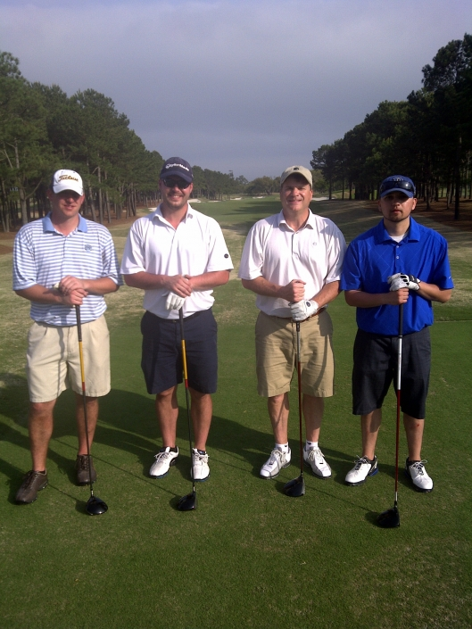 Four men holding golf clubs on a golf course.
