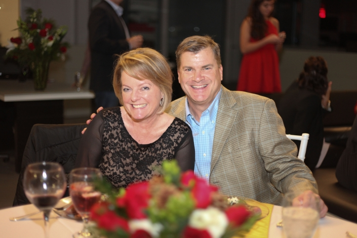Denise and Ryan Legg at the MegaCorp holiday party in 2015. They are sitting at a table and smiling.