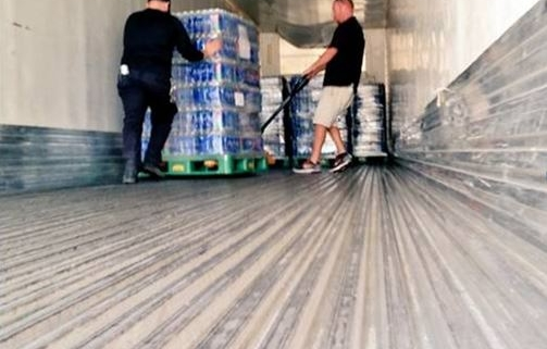 Two men unloading the trailer of a MegaLines truck. They are operating a trolley that is carrying a stack of five cases of bottled water.