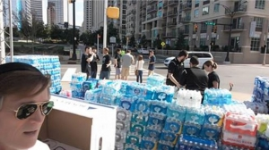 Several large stacks of cases of bottled water and sports drinks, just unloaded from the truck.