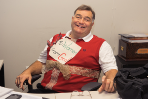 A smiling man in a red sweater-vest. He has a lacey ribbon tied around his torso like a gift. Also tied to his sweater is a piece of paper, cut to look like a gift tag that reads,