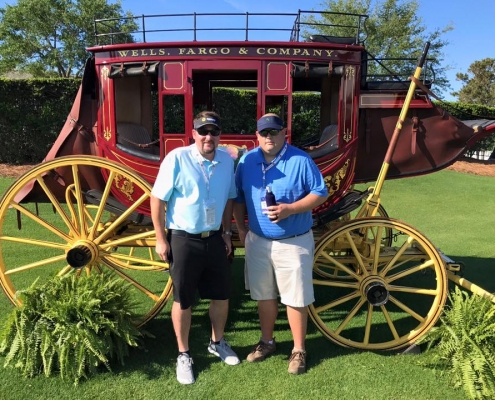 Two men posing in front of a horse carriage in the grass. Wells Fargo & Company is printed on the side.