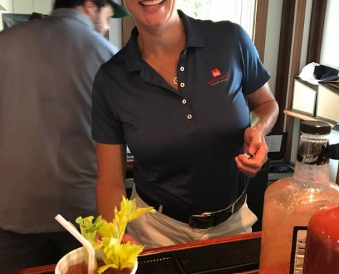 A woman wearing a Wells Fargo shirt smiling from behind a bar. There is a Bloody Mary in a styrofoam cup sitting on the bar. The cup has the MegaCorp logo printed on it.