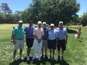Six men posing on a golf course on a sunny day.