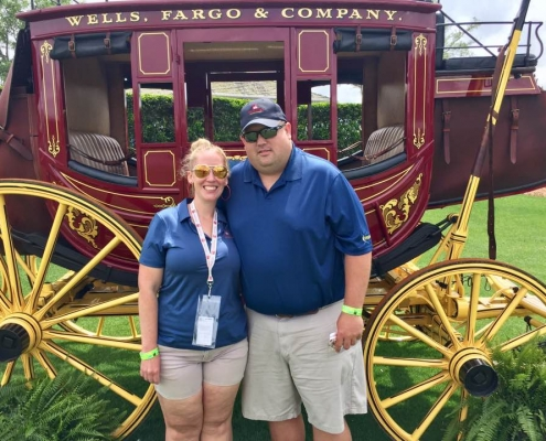 "A man and a woman smiling and embracing in front of a horse carriage that has ""Wells Fargo"" printed on the side."