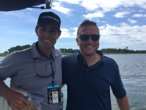 Two men smiling while in a boat on a fishing trip.