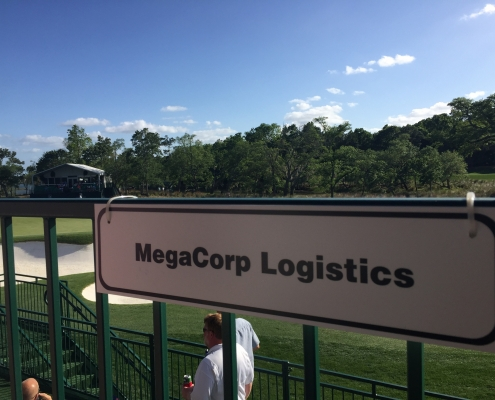 "A green golf course on a bright day. There is a sign that reads, ""MegaCorp Logistics"""