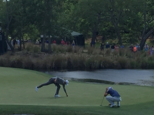 Two men are playing golf by a pond. They are both crouched over to set the ball in place.