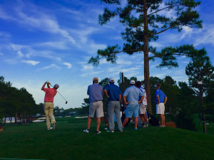 A group of people watch as a man swings his golf club on a clear, blue-skied day.