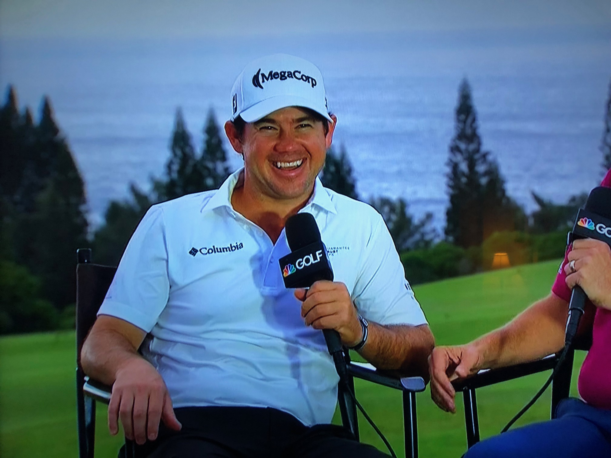 Professional golfer Brian Harman during an interview. He is sitting in a chair in front of a background that depicts a golf course, wearing a MegaCorp hat and holding a microphone with the NBC Golf Channel logo.