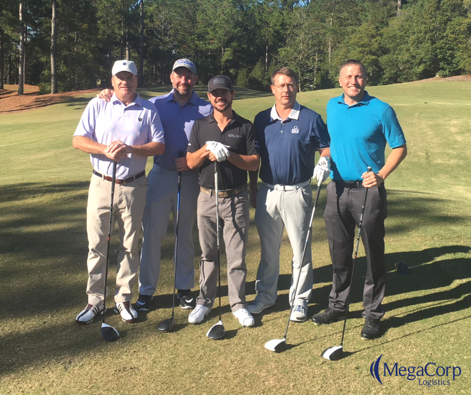 Four smiling men with Brian Harman on a golf course. They are all holding golf clubs in front of them.