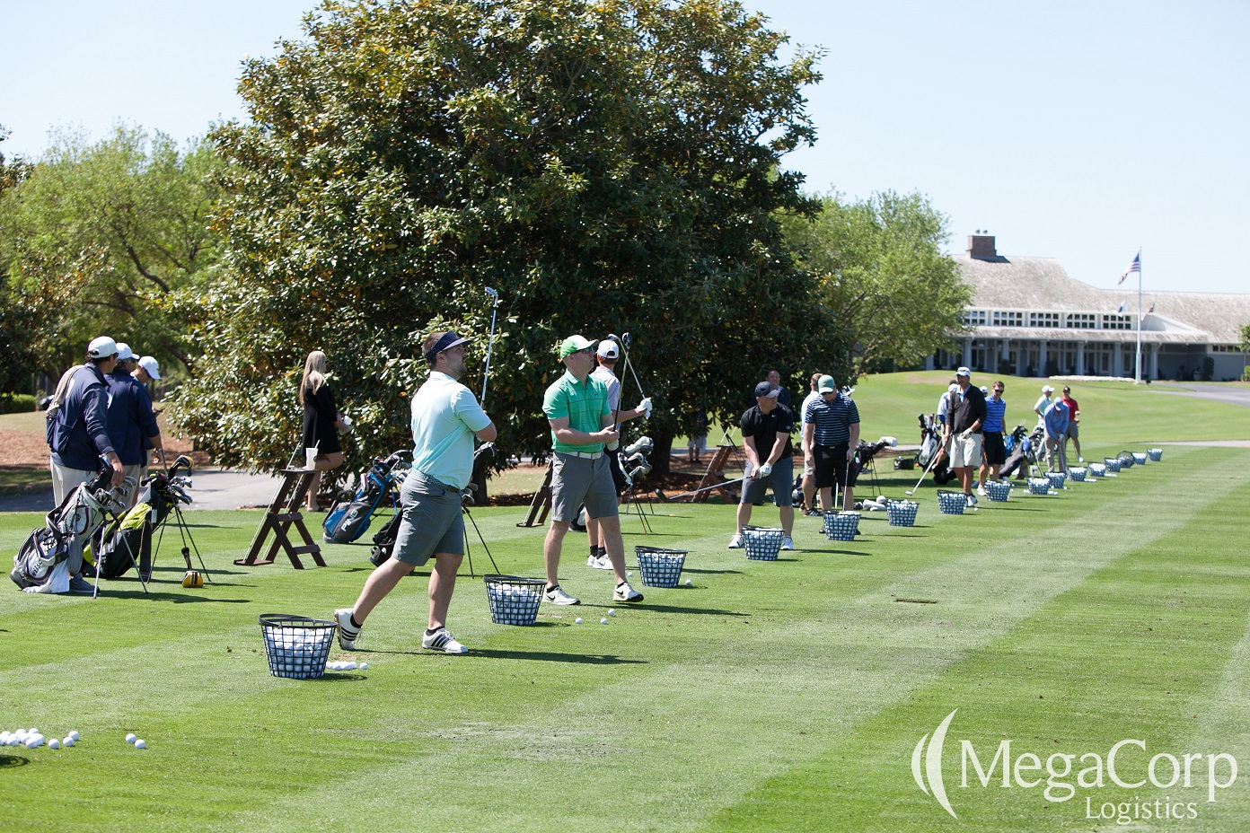 Baskets full of golf balls lining the green grass. A few men are hitting the golf balls and looking into the distance.