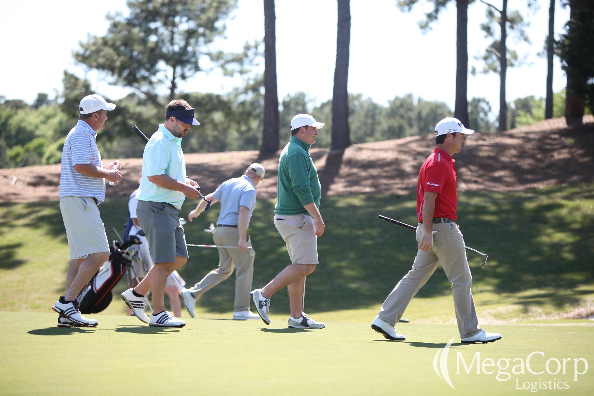 Five men walking across a golf course, clubs in hand.