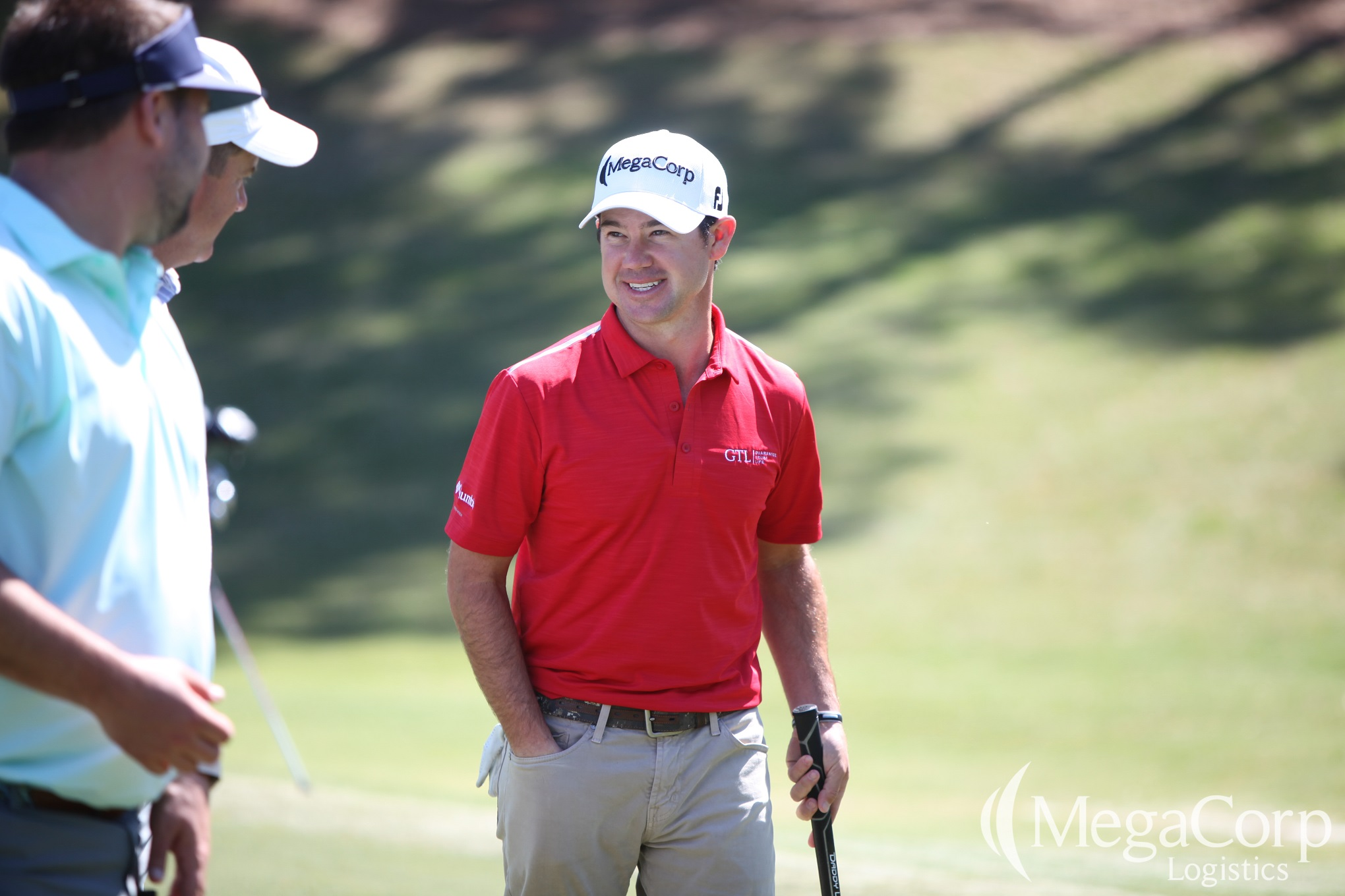 Brian Harman, smiling and wearing his MegaCorp hat, engages in conversation with two men on the golf course.