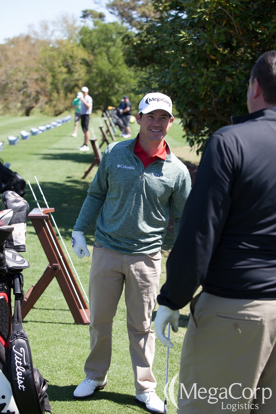 Brian Harman smiling and holding a golf club while talking to another man on the golf course.