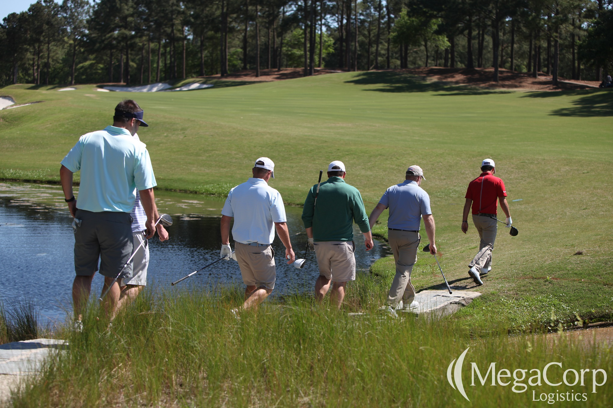 Six men, carrying golf clubs while walking by a golf course pond.