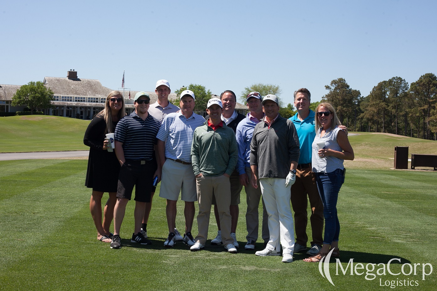 Brian posing with multiple smiling members of the MegaFamily on a golf course.