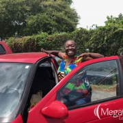 A smiling woman doing a 'happy dance' next to a red car.