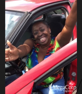 A woman sitting in the drivers' seat of a red car. She is smiling and extending her arms in joy.