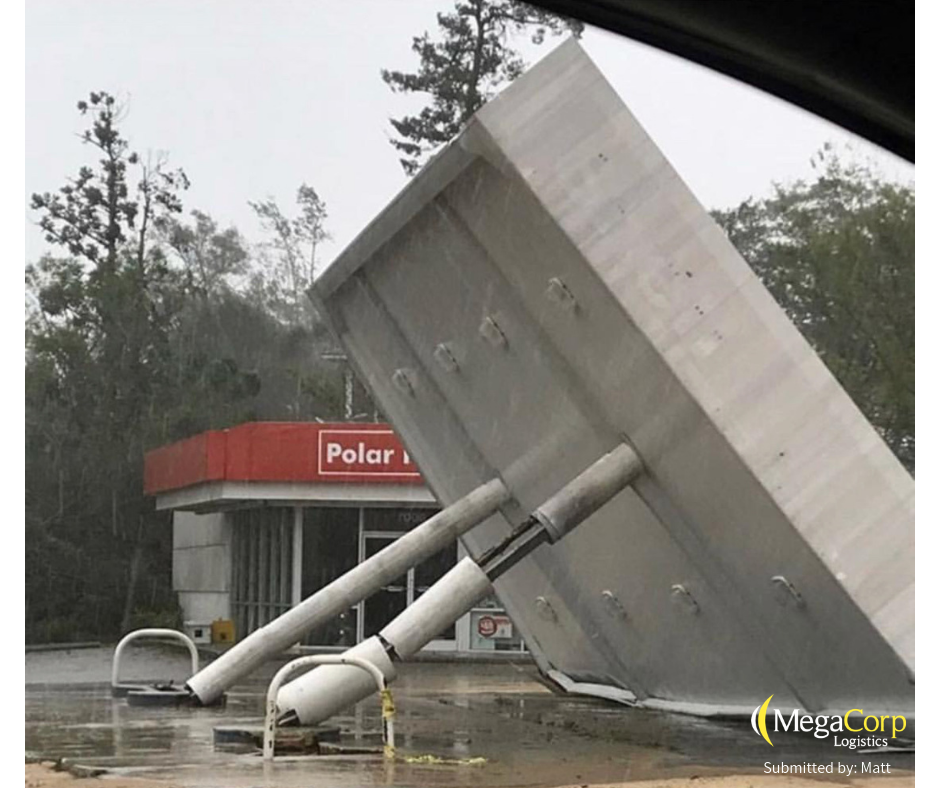 A gas station knocked over on its side by the winds.