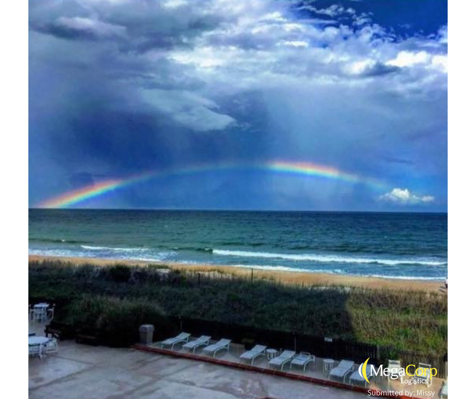 A rainbow peeking through dark, ominous storm clouds over the ocean.