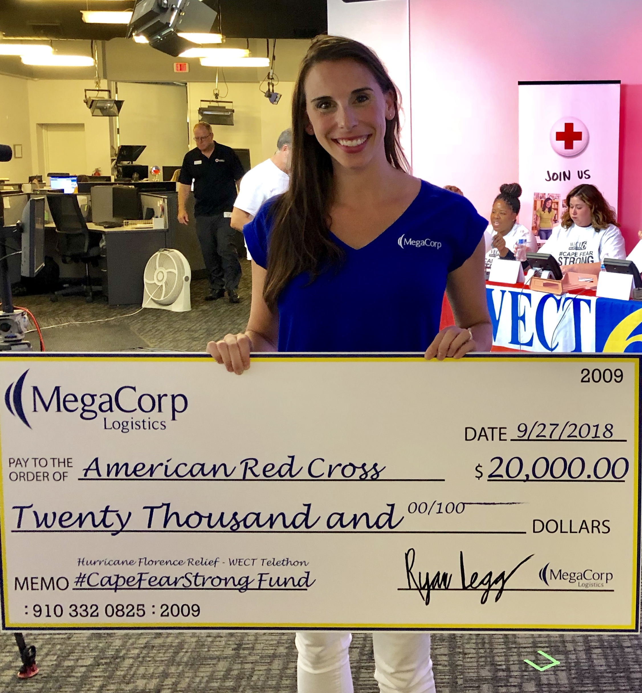 Katie holding up a giant check made out to the American Red Cross for $20,000 for Hurricane Florence Relief.