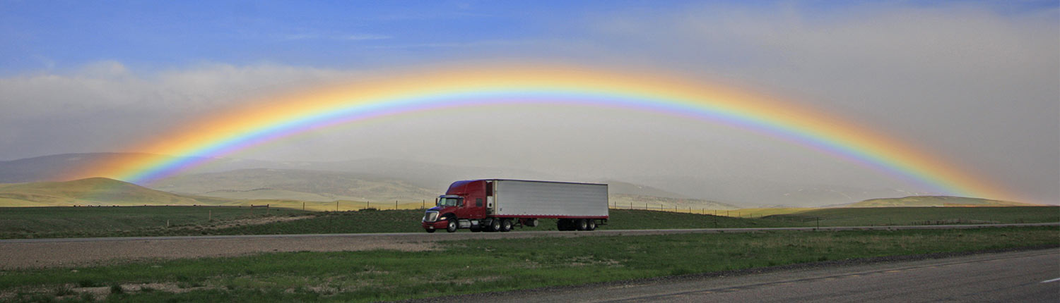 Carrier Truck driving under a rainbow